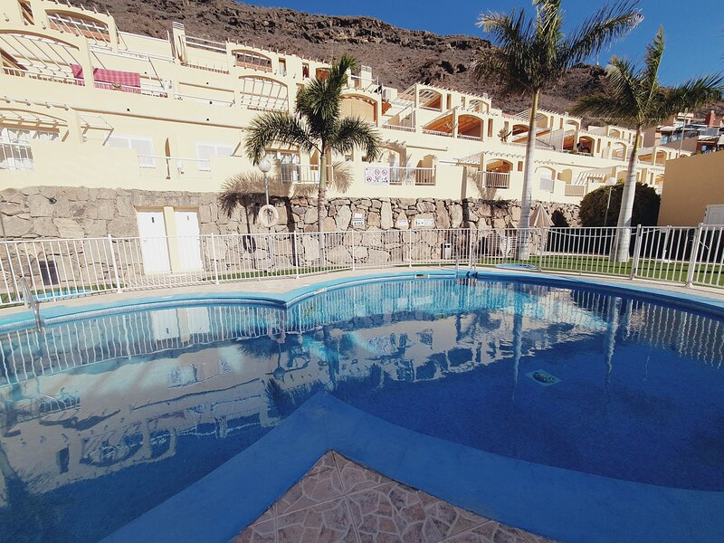Apartamento encima de la piscina con vistas a la montana, aluguéis de temporada em Taurito