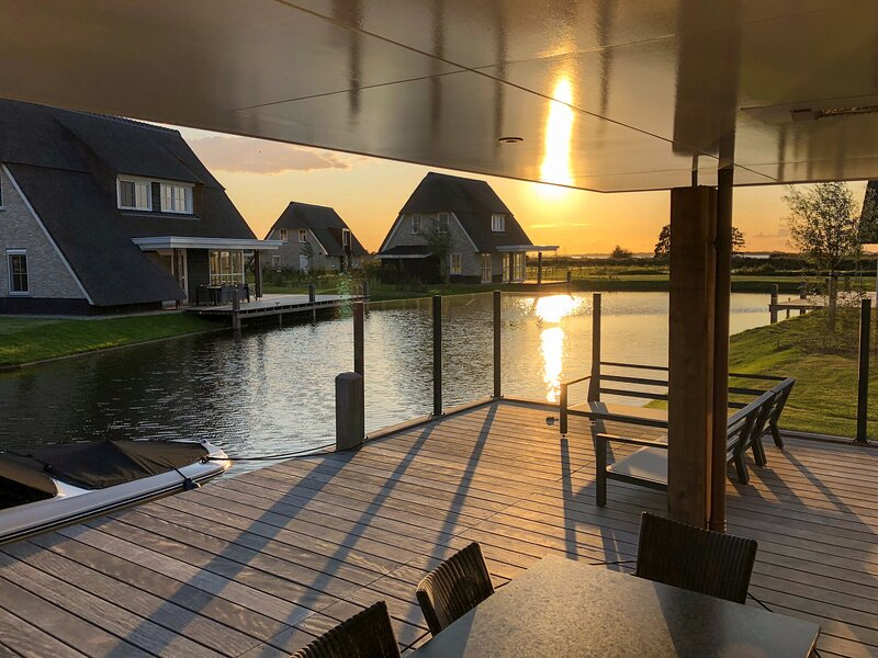 Thatched villa with lounge set, right at the water, holiday rental in Sint Nicolaasga