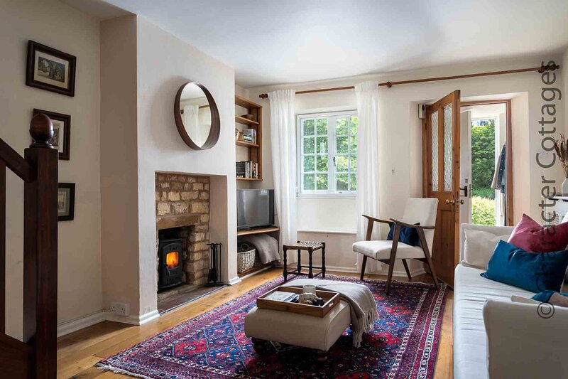 The stylish living room contains a lovely fireplace with a wood burning stove