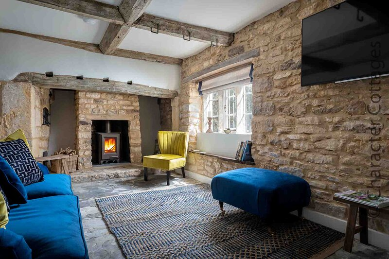 The stylish living room contains an impressive inglenook fireplace with a wood burning stove