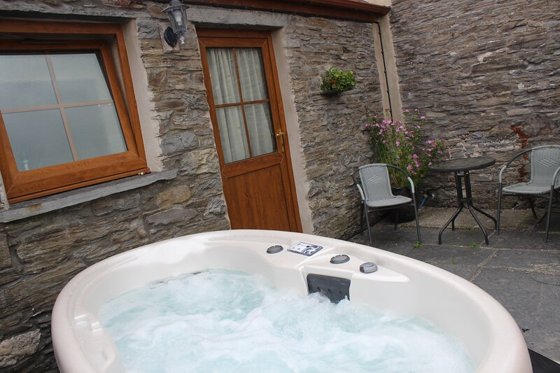 Hot tub in gorgeous private patio area with original slate and stone