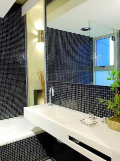 Bathroom has rainfall from the ceiling shower, bathtub, toilette and bidet