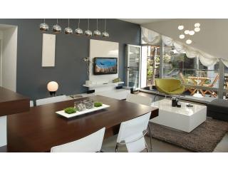 Coin salon avec meubles faits sur commande, télévision LCD et accès au balcon