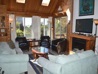 Middle endry level living room with wall mounted flat screen cable TV/Blu-Ray DVD, electric fireplace, couch, loveseat, three leather arm chairs and a small reading corner with books and a bench.