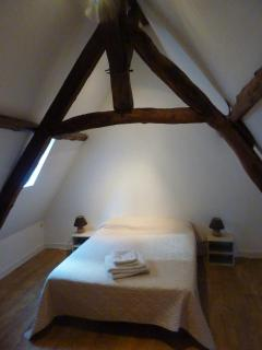 one of the 2 2nd floor bedrooms each with exposed beams