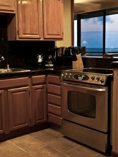 Stainless appliances, unusual granite reflects the aqua of the ocean.