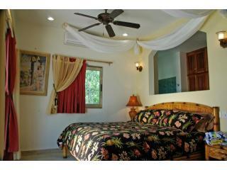 Abajo aire acondicionado dormitorio con deslizante de cristal que se abre hacia la playa y la bahía de Tankah