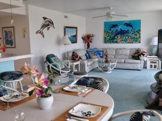 Bright, open living/dining room with Flat screen TV  and large sliding doors open to the Lani.