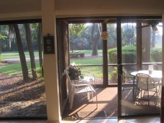 LARGE SCREENED PORCH WITH CEILING FAN OVERLOOKING GOLF COURSE.