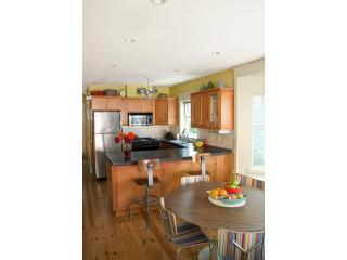 Kitchen with stainless appliances and modern and vintage furniture, mountain view, balcony