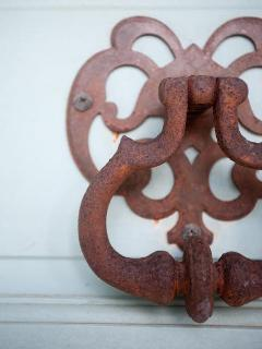 Closer view of the knocker with a patina of rust.