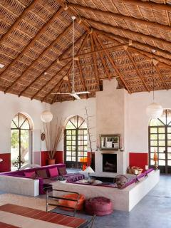 The living room, sunken  couch, fireplace, palapa roof (palm leaves roof)