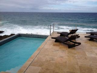 Relax in one of our lounge chairs overlooking the pool and the  Caribbean