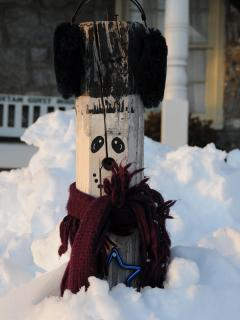 The Antietam Guest House 'Postman' wears earmuffs and a scarf in the snow.