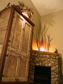 Entertainment armoire and riverstone fireplace