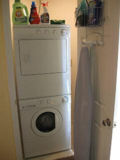 Laundry room with washer/ dryer, iron & board, supplied with laundry detergent.