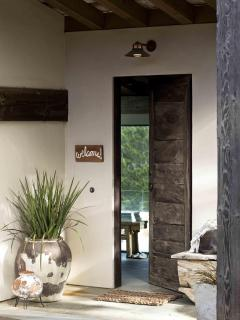 100 year old oversize teak door pivots for effortless opening.
