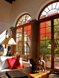 THE 15 FT. TALL WINDOWS MAKE THE ROOM BRIGHT AND ALLOW FOR A LOVELY VIEW OUT TO THE GARDEN AND POOL.