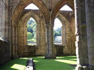 Tintern Abbey Cottage seen though the arched windows of the Abbey Nave. We are so close!