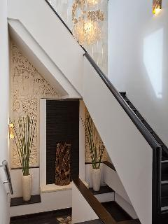 Staircase connecting three floors decorated with Balinese stone carving and Rama and Sita statue.