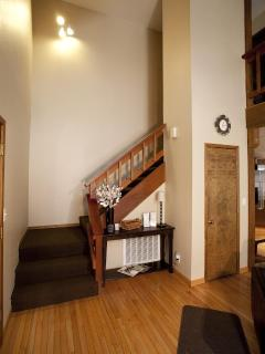 Stairs leading to bedrooms, second bathroom with tub, game loft, and laundry facilities.