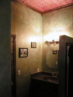 Guest Bathroom with copper sink and ceiling and hand-made stone floor tiles.