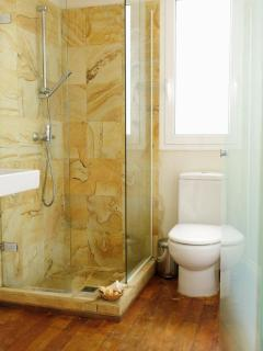 1º Bathroom with wooden floor and shower with stone walls