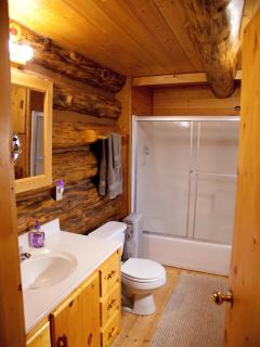 Comfortable sized bathroom with full size tub & shower and full size washer & dryer. (behind door)