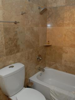 One Bedroom Suite Travertine Tile Throught the Bathroom