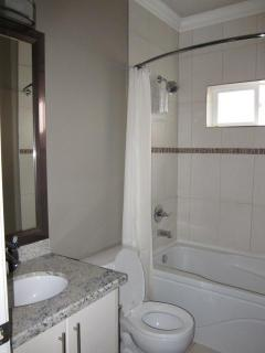 Bathroom with soaker tub with shower, curved hotel style shower curtain