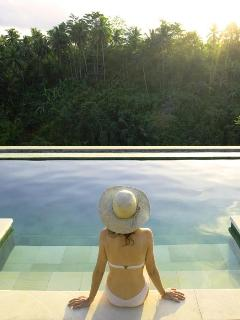 Guest enjoying herself by the infinity pool overlooking the dramatic surrounding vistas