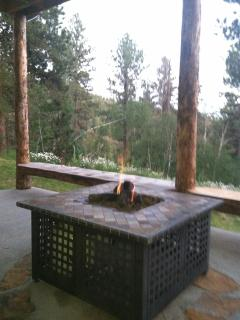 gas fire pit on lower level with chairs and wooden banks