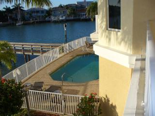 View of heated pool from balcony with access to lounge chairs for your enjoyment