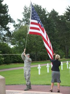 Lowering the flag at Taps Coleville Sur Mer American Cemetery