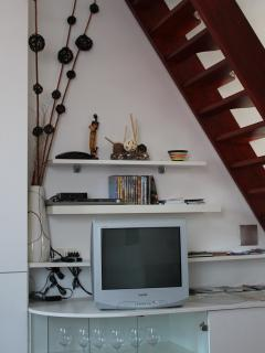 TV , DVD player, alarm clock and stairs to upstairs bedroom