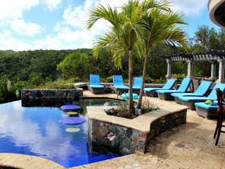 Island Stones pool deck has 8 chaise lounge chairs and tables with chairs