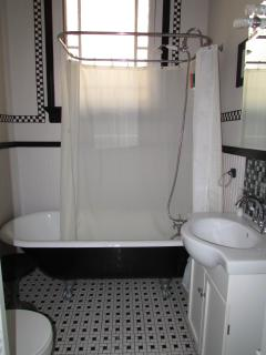 Bathroom is freshly renovated and features clawfoot tub with shower
