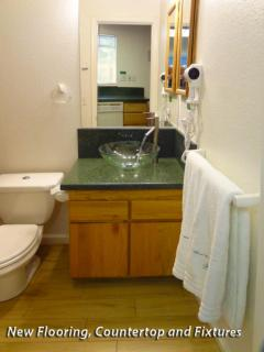 Remodeled bathroom with countertop, flooring, and fixtures