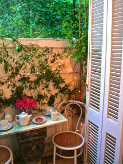 Small plant-filled outdoor balcony with marble topped table for two