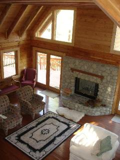 Big stone fireplace, lots of windows & French doors to the deck.