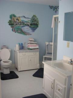 spacious bathroom with shower stall, sink and toilet