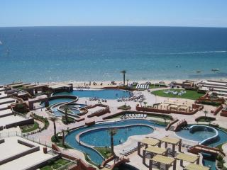 View from our balcony overlooking the courtyard with lazy river, water slide, pools, and swimup bar