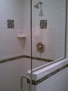 Ceramic tile walk in shower with glass wall and door