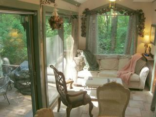 Sunroom: lots of windows & skylights looks out to the back deck w/hot tub & patio dining & forest
