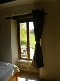 The full size window in the bedroom provides a lovely view over the south facing garden & pool area