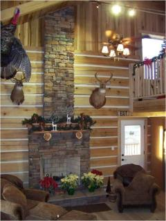 A large living area with wood-burning stone fireplace and cathedral ceilings is on the main level