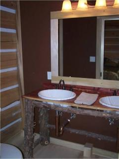 The Deer bathroom offers a double vanity with custom cedar vanity and shower/tub combination