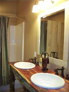The Horse Bathroom offers a double vanity with custom cedar vanity and shower/tub combination