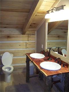 The Pheasant Bathroom offers a custom double vanity made of beautiful red cedar and a shower/tub