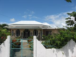One-storey Dolphin villa & its Dolphin gates against the background of a typical blue Tobago sky.
